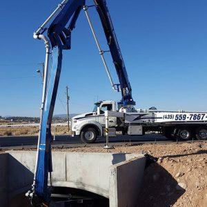 Concrete pumper boom extended around into culvert beneath roadway