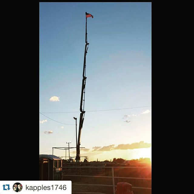 Truck with boom extended straight up with American flag on top