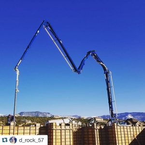 Truck extending boom over tall wall forms