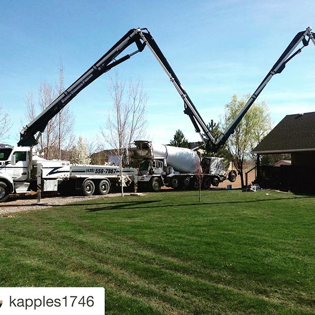 Concrete pumper boom extended across nicely manicured lawn
