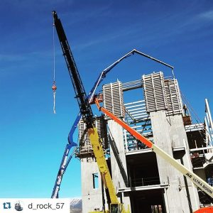 Concrete pumper boom extended to full height pouring a high-rise building
