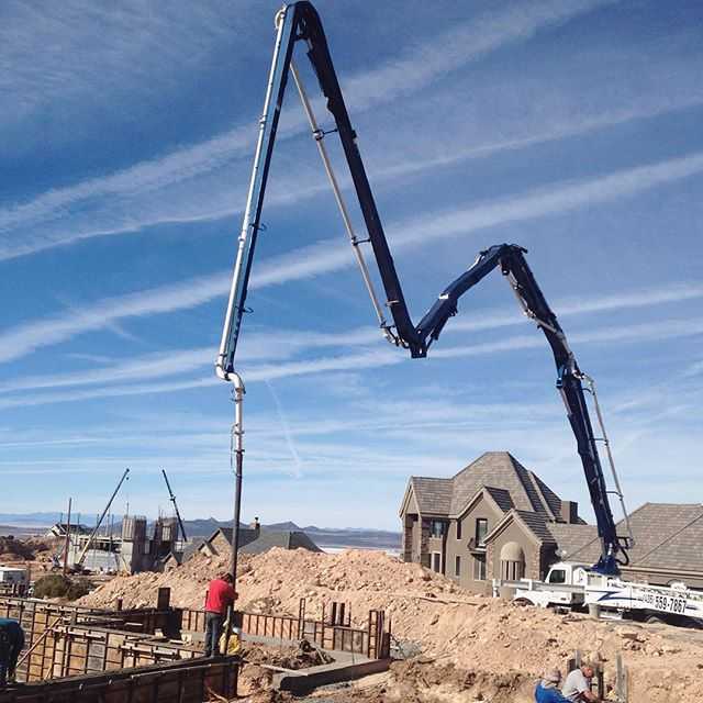 Boom extending over construction site to pour basement wall