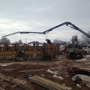 Boom reaching across construction site to pour tall wall