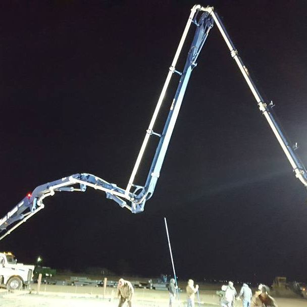 Concrete pumper boom extended at night