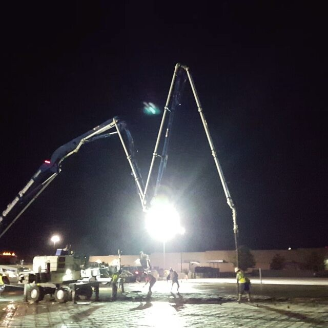 Workers pouring slab under lights at night