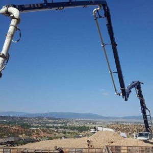 Concrete pumper boom extended over foundation walls with nice view in background