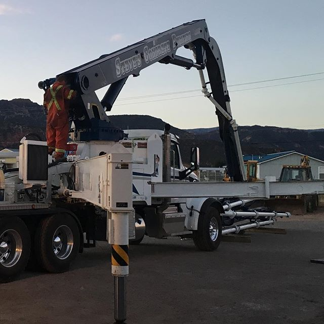 Worker up on truck inspecting the boom