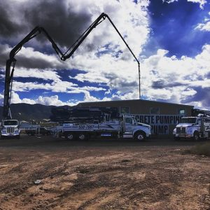 Three pumper trucks, one with boom extended