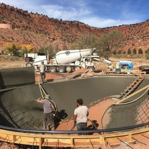 Workers blasting shotcrete on curved walls for skate park