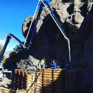 Concrete boom extended over tall foundation walls next to large rock outcropping
