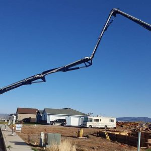 Concrete pumper boom extended to reach foundation walls in new neighborhood