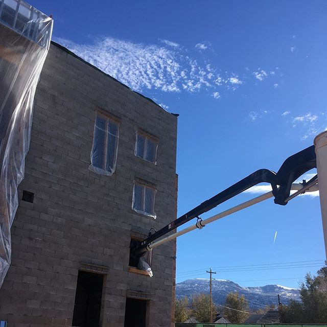 Concrete pumper boom reaching into open window of building