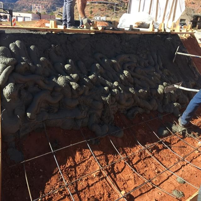 Workers smoothing out concrete for skate park walls