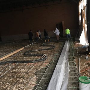 Workers pouring indoor slab with the line pump